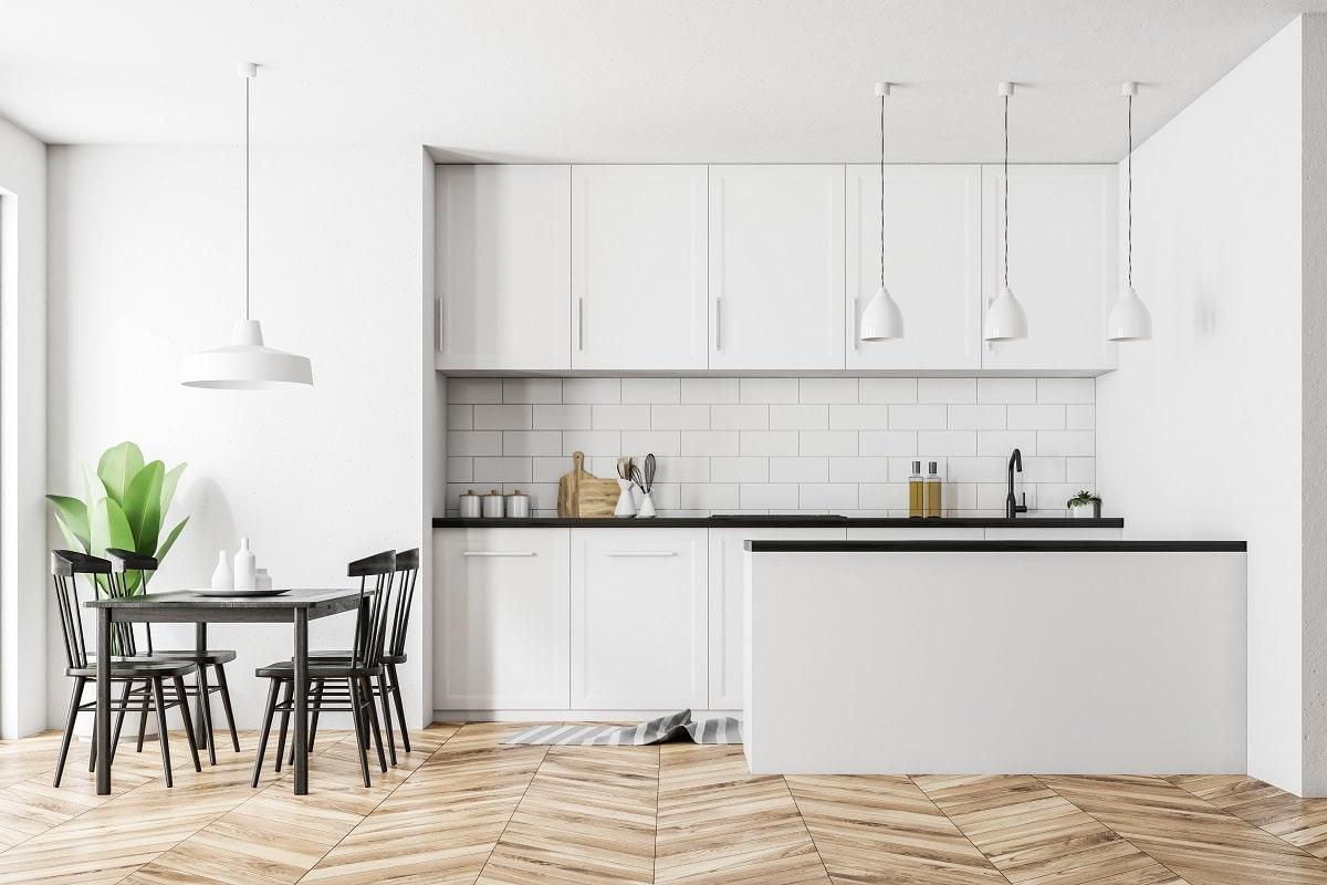 Einfallendes Tageslicht und weiche Farben kreieren eine besonders freundliche Atmosphäre, in diesem Wohnraum. Die Küche wirkt aufgrund der kürzeren Länge der im Raum stehenden Küchenzeile offen und einladend. (Foto: Stock Adobe/denisismagilov)