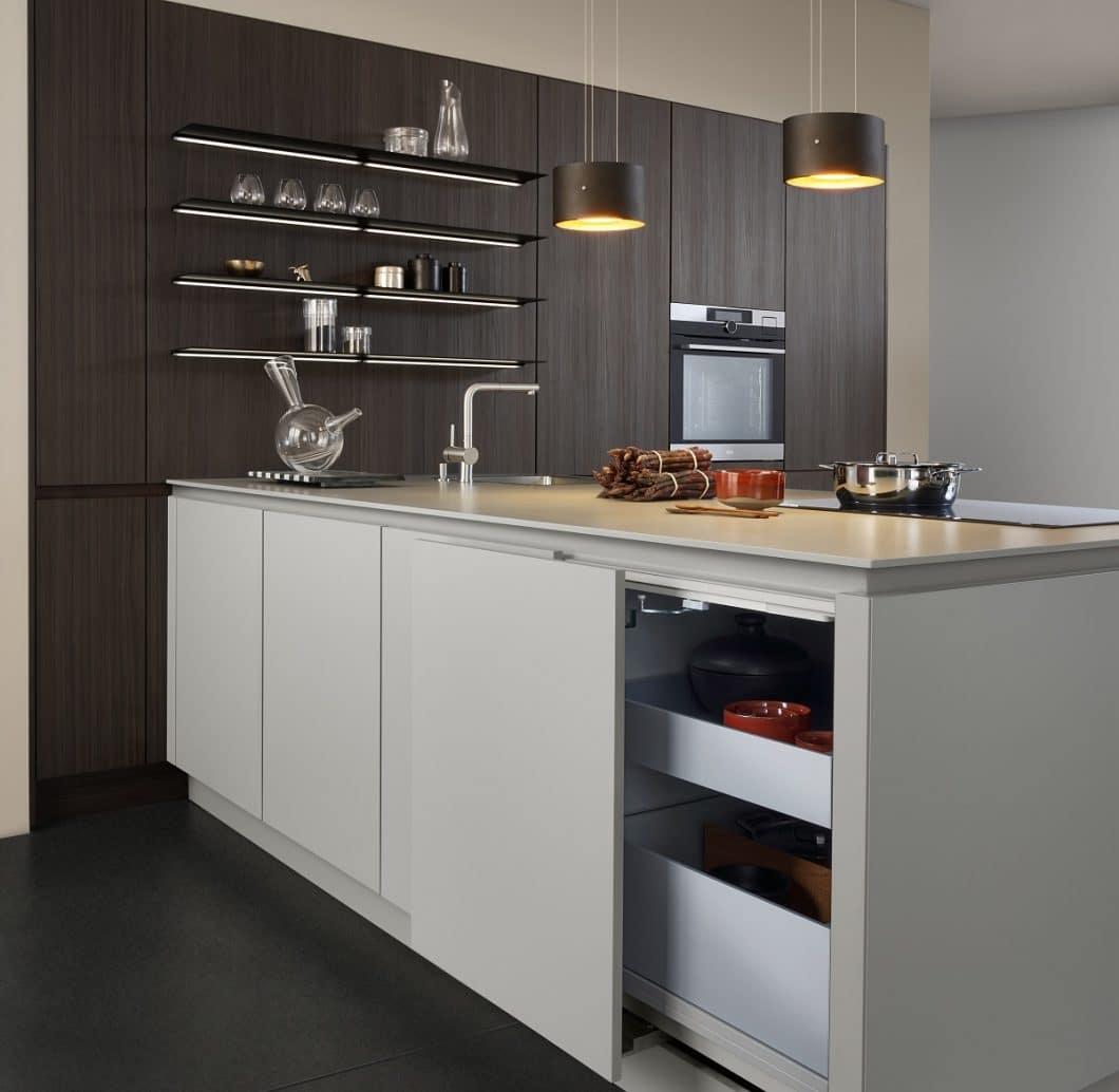 Strukturiertes, dunkles Holz trifft auf glatte, grifflose Oberflächen in hellem Oliv. LEICHT setzt seine Materialcollagen geschickt zusammen - und erschafft so neue Impulse im Küchenraum. (Foto: LEICHT)