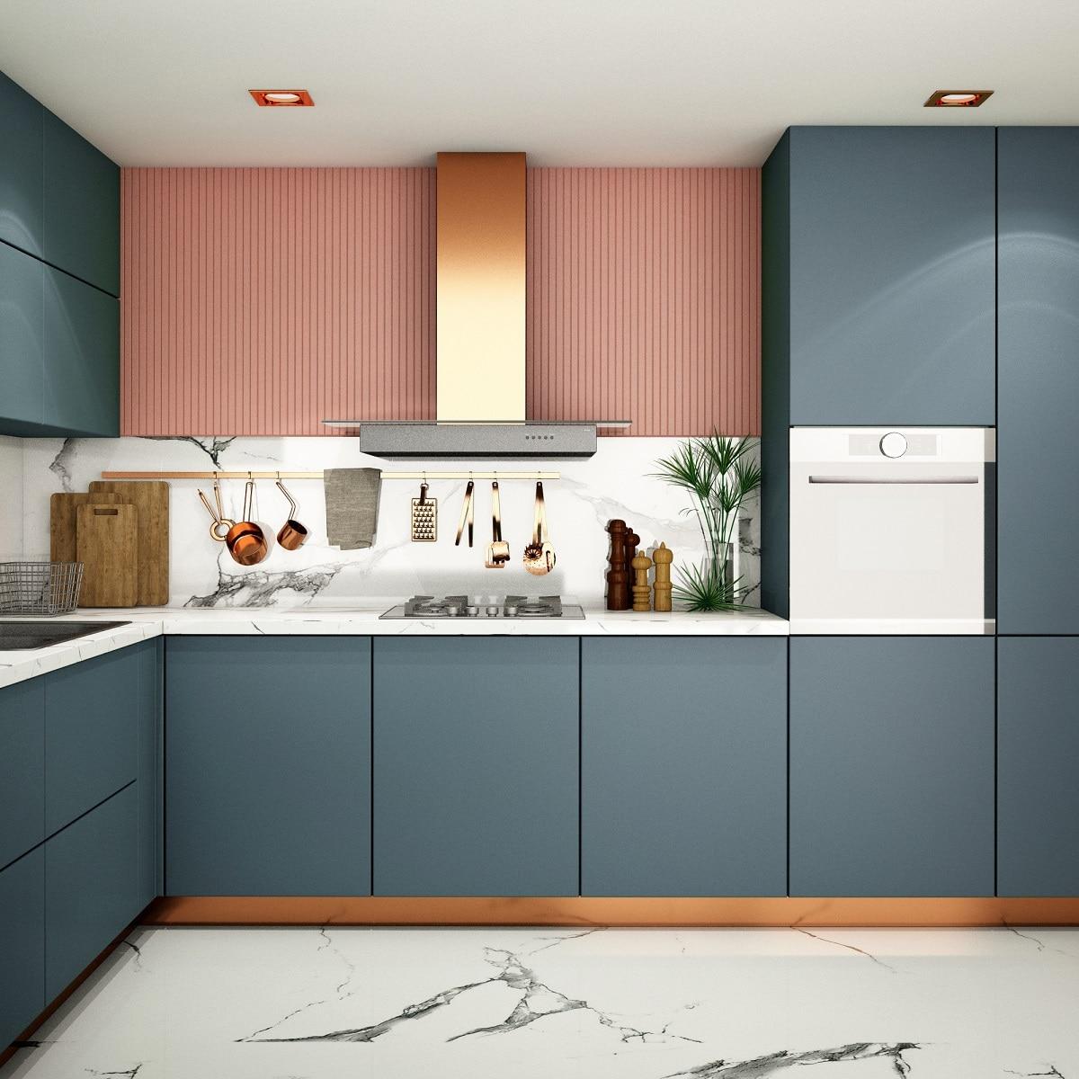 Ein farbenfrohes Trio bilden die graublauen Küchenschränke, die roséfarbene Rückwand und die Elemente in Marmoroptik. Ein besonderes Schmankerl sind Dampfabzug und zurückgezogener Sockel in Kupfer. (Foto: Stock Adobe/TATTA)
