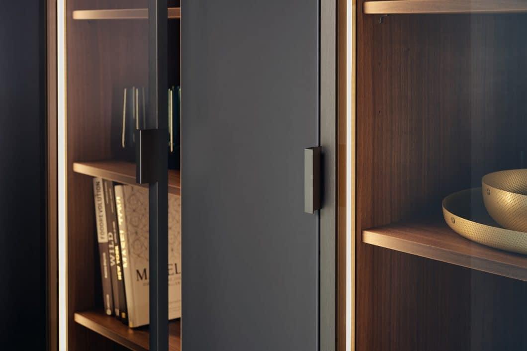 Warmes Walnussholz, das von schmalen Metallstreben eingefasst wird, sorgt für elegante Kontraste zwischen den glatten Stahlfronten der Küchenzeile. (Foto: LEICHT)