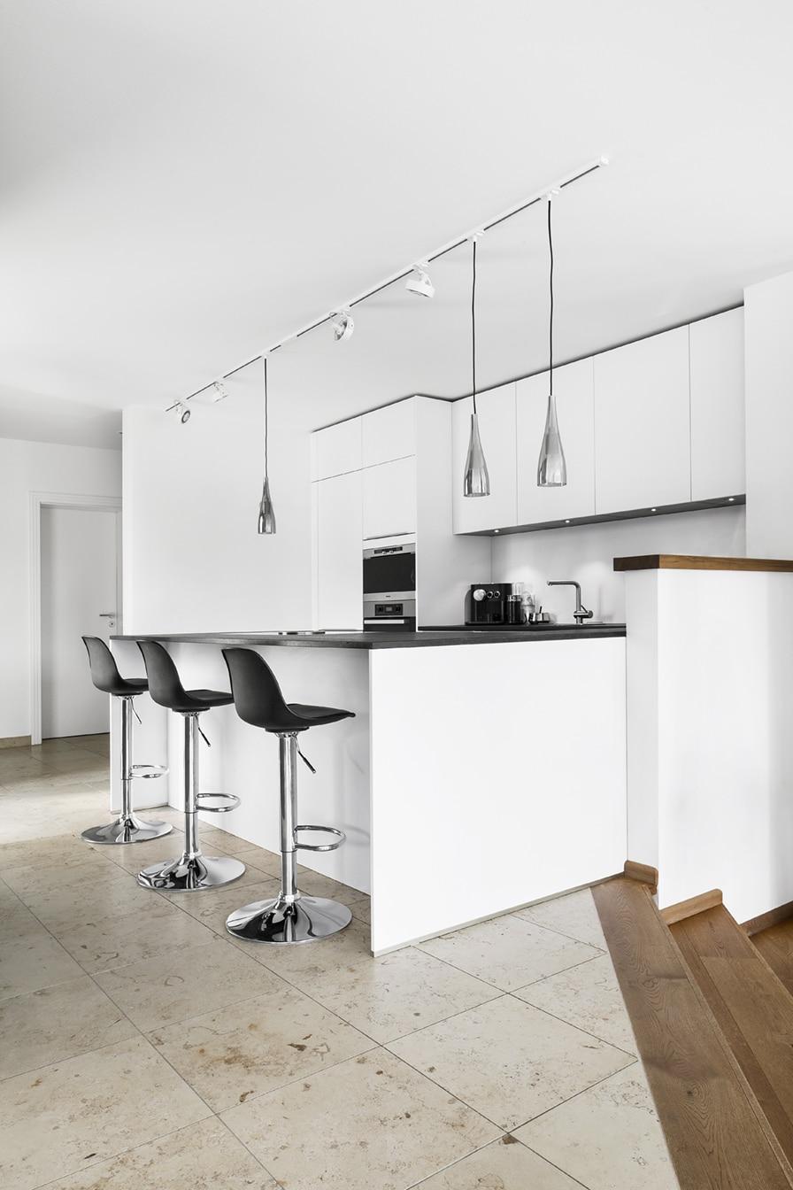Puristisch, schlicht, schwarz-weiß: wie ein ästhetisches Stillleben fügt sich die Küche unberührt in den Wohnraum ein. Bis die junge Familie sie mit Leben füllt. (Foto: Dross Ingolstadt)