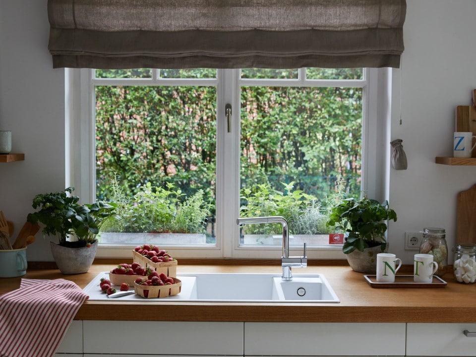 """Eine Armatur direkt vor dem Fenster bietet einen wunderschönen Ausblick beim Spülen. Allerdings sollten sich Verbraucher nach sogenannten """"Vorfensterarmaturen"""" erkundigen: sie können umgelegt werden, um das Fenster flexibel zu öffnen und zu schließen. (Foto: BLANCO)"""