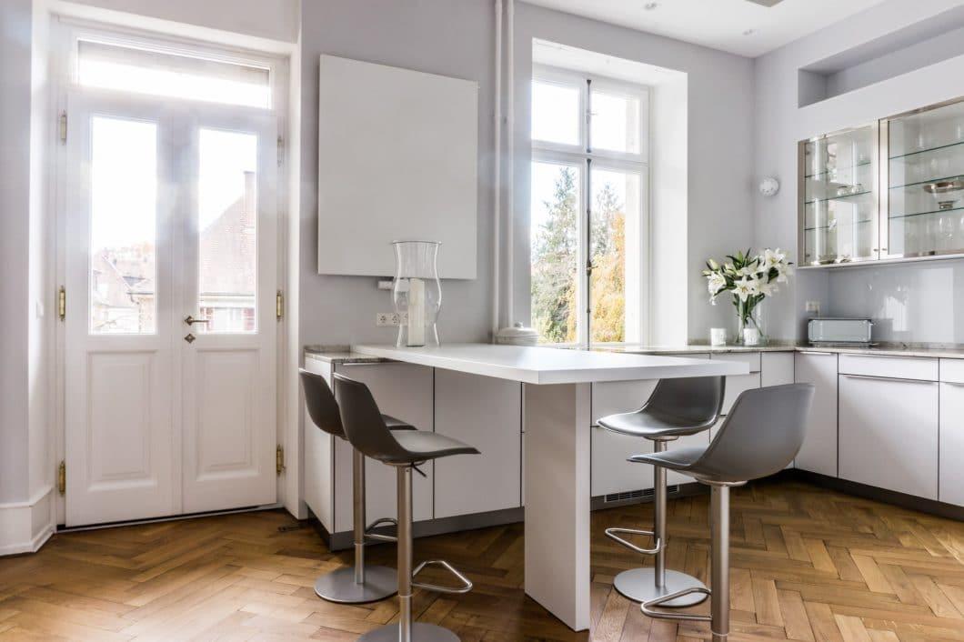 Hochwertige Glasfronten in einem sanften Merino-Farbton treffen bei dieser LEICHT-Küche auf eine schmal verarbeitete Arbeitsplatte aus Granit bianco romano poliert - und ein edel aufbereitetes Fischgrätenparkett aus Holz. (Foto: Andreas Schaps)