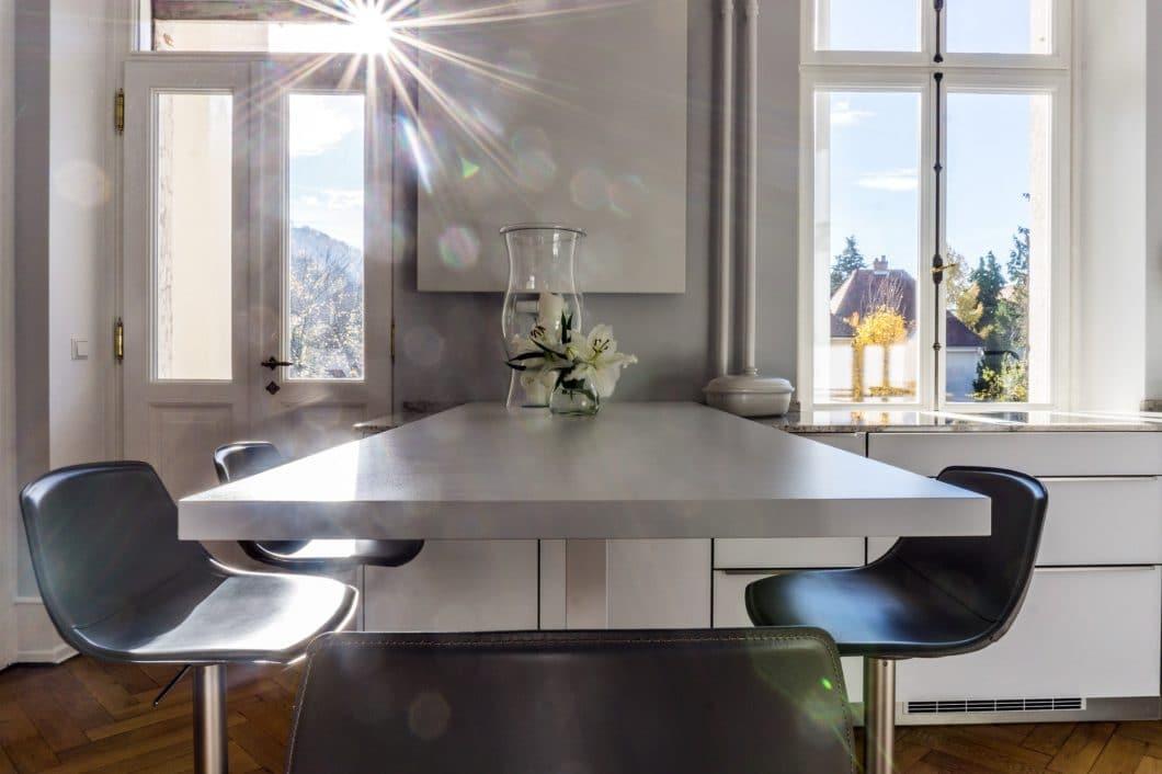 Die großzügige Fensterfront der Freiburger Gründerzeitvilla spielt nun als Ausblick beim Kochen eine tragende Rolle. Geschickt itnegriert wurde eine weiße Heizplatte über dem Essbereich. (Foto: Andreas Schaps)