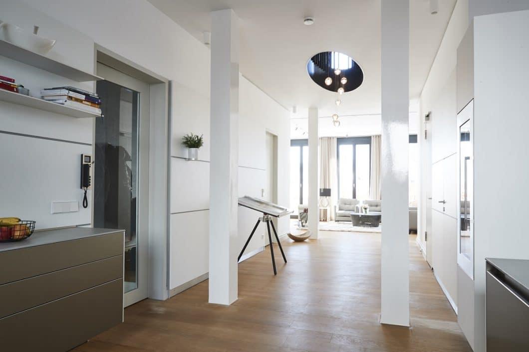 Küchen- und Wohnraum werden über die puristische bulthaup-Paneelwand miteinander verbunden. Auch das bulthaup b3-Schrankmodul neben der Eingangstür knüpft an die Küche an. (Foto: Küchen-Atelier Hamburg/ Volker Renner)