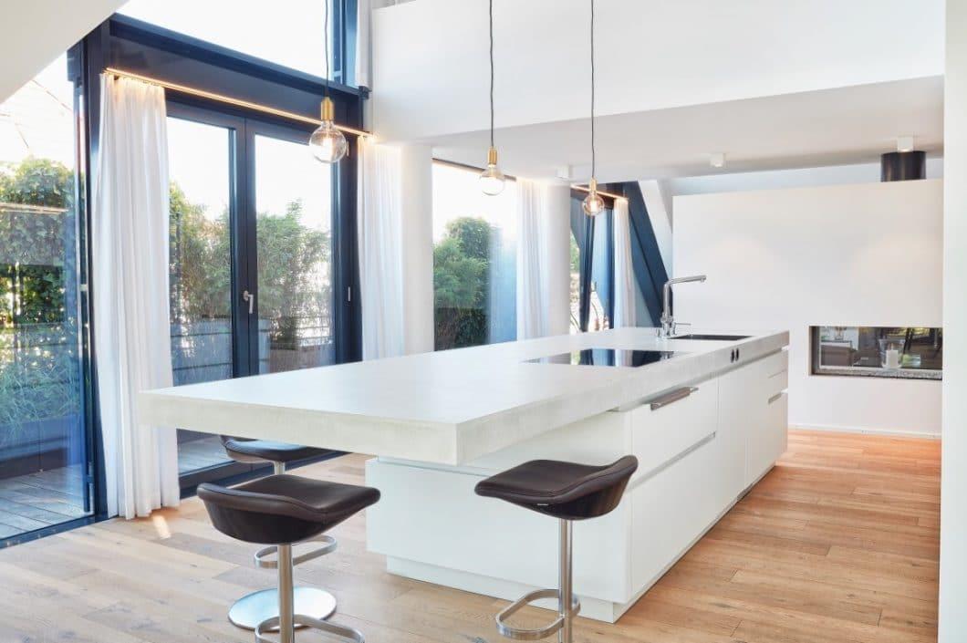 Blick aus dem Fenster auf den Ort, an dem die Kundin aufgewachsen ist: das gesamte Küchenprojekt ist voller sanfter Reminiszenzen an den Lebensweg der Dame. So beispielsweise auch dei Beton-Arbeitsplatte. (Foto: Ralph Koch/ Küchenkunst Einbaukunst)