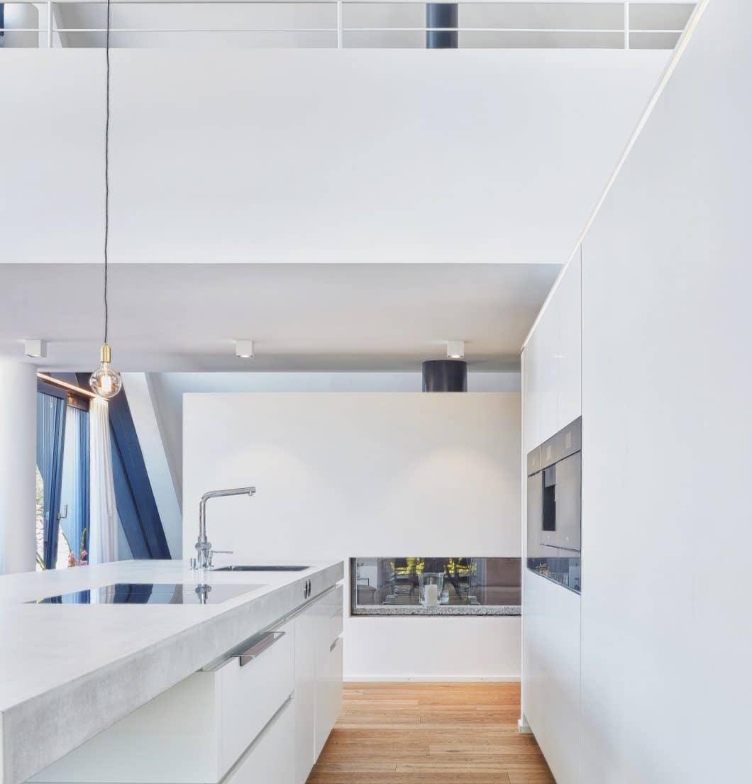 Das von der Galerie aus einsehbare Loft wurde mit einer weichen und warmen Lichtplanung versehen. Passend zur gewünschten Atmosphäre kann diese im Küchenraum ebenso angepasst werden. (Foto: Ralph Koch/ Küchenkunst Einbaukunst)