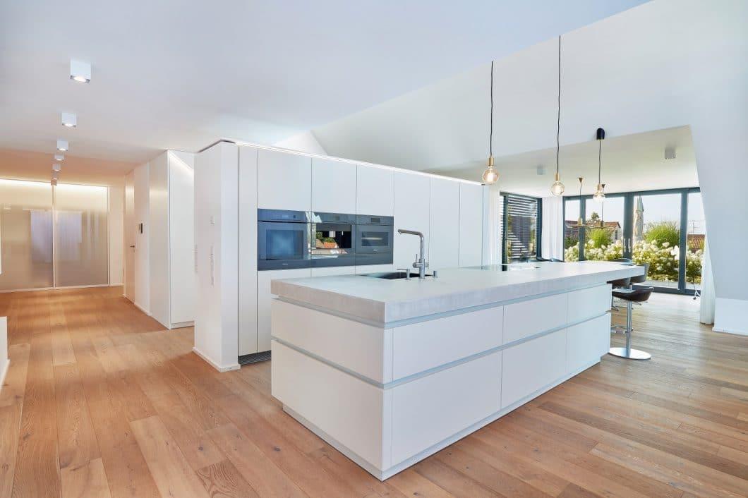 Die offen in den lichtdurchfluteten Raum eingebundene Architekturküche erstreckt sich zentral angeordnet zwischen Essplatz am Fenster und einem Wohnbereich mit Kamin. Im Hintergrund versteckt sich ein begehbarer Hauswirtschaftsraum, maßangepasst an die darüberliegende Treppe. (Foto: Ralph Koch/ Küchenkunst Einbaukunst)