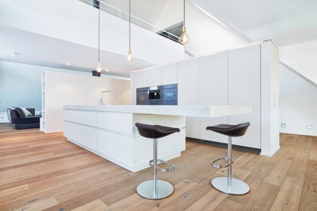 Die offene weiße Architekturküche fügt sich zurückhaltend und doch präsent in das Loft ein. Ihre Planung geht auf die Lebenswege der Kundin zurück. (Foto: Ralph Koch/ Küchenkunst Einbaukunst)