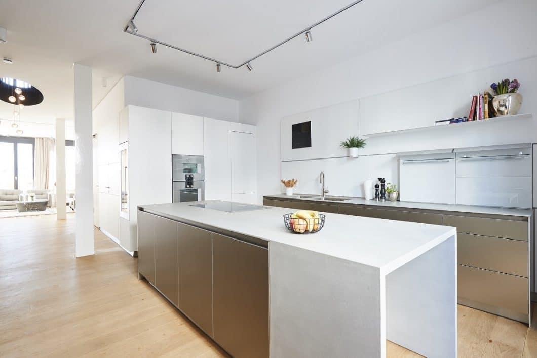 Für diese Beton-Arbeitsplatte wurde eine spezielle Verschalung benötigt. Das Ergebnis wurde vor Ort behutsam an den Küchenraum angepasst. Auch die Bodenverlegung und Lichtplanung wurden zeitgleich koordiniert: gut, wer mit einem Küchenplaner an der Hand den Überblick behält. (Foto: Küchen-Atelier Hamburg)