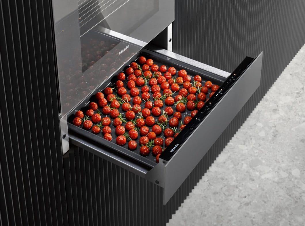 Haben Sie schon mal daran gedacht, Wärmeschubladen in der Küche auf diese Weise zu nutzen? Das Dörren von Obst oder das Niedriggaren von Gemüse kann eine attraktive Nutzung der zusätzlichen Schublade sein. (Foto: Miele)