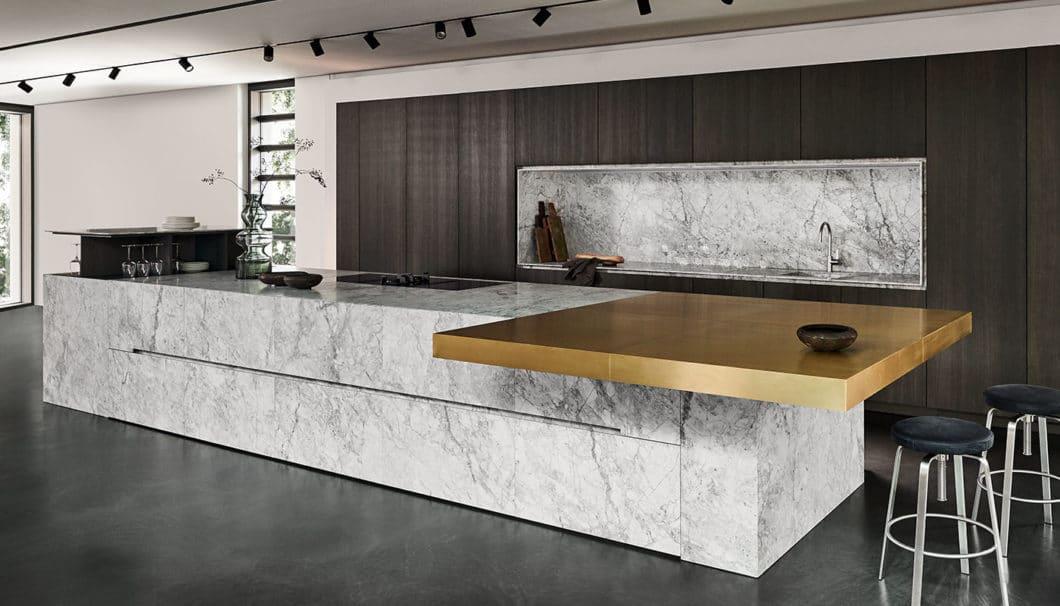 Modell 1 setzt den voluminösen Quarzitblock Bianco Nuvola in Szene. Eine dunkle Wand aus Kernesche und ein messingfarbener Küchenblock dienen als Gegenpol. (Foto: eggersmann)