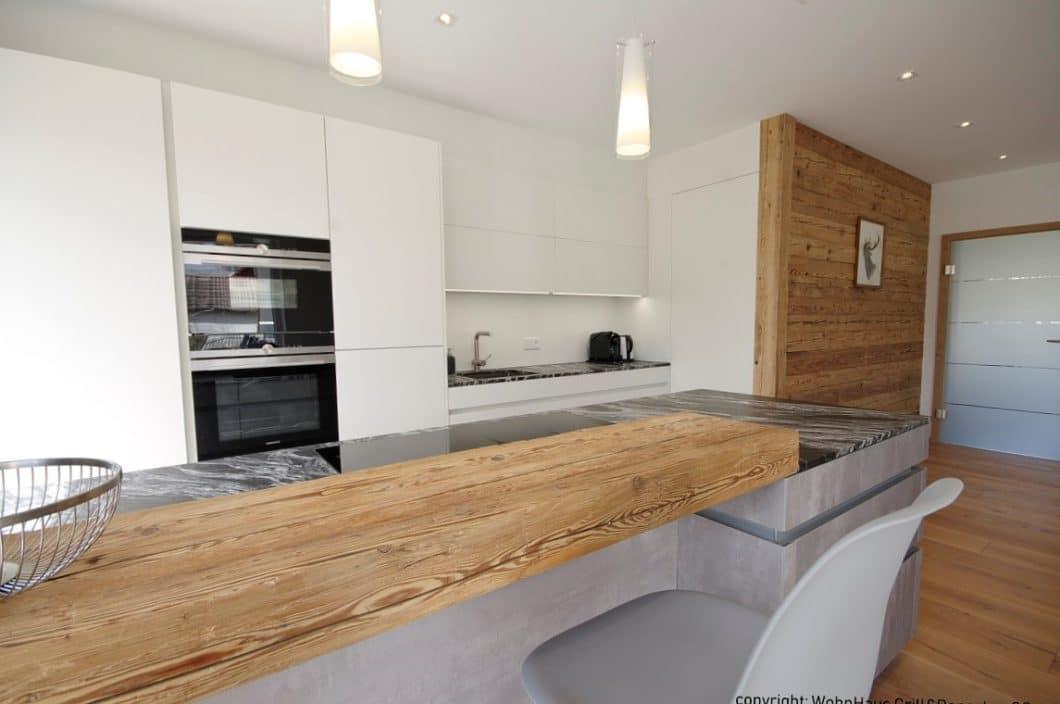 Für den modernen Küchenraum setzt Grill & Ronacher geschickt auf eine ruhige Dreifarbigkeit: Weiß, Beton und Braun in Form von edlem Altholz wechseln sich ab. (Foto: Wohnhaus Grill & Ronacher)