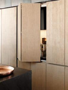 Hinter der faltbaren Tür aus Eichenholz verbirgt sich ein Pocketschrank, in dem Küchenkleingeräte Platz finden. (Foto: eggersmann)