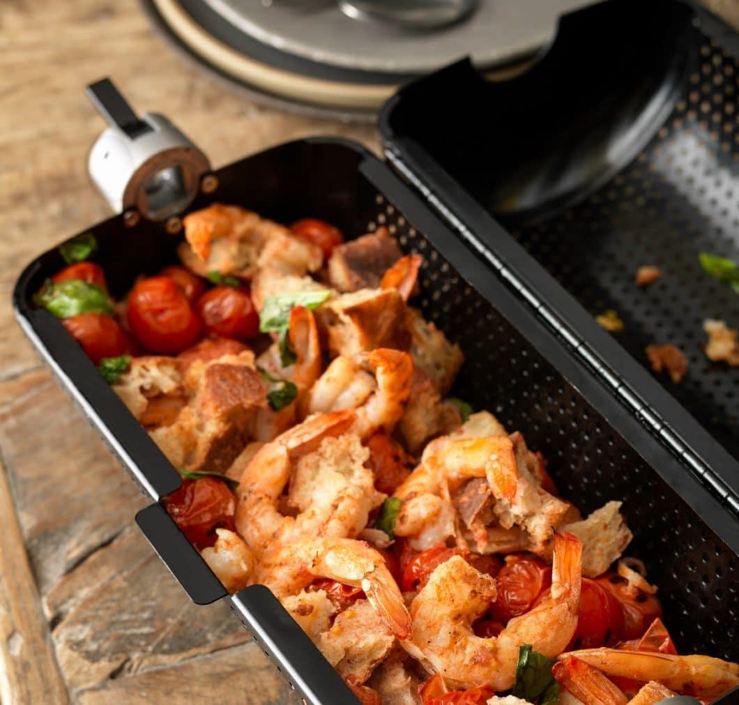 Smarte Grill-Utensilien: ein Rotisserie-Korb nimmt beispielsweise auch ganze Gerichte im Inneren auf und schmort diese gleichmäßig von allen Seiten. Zum Extra-Zubehör zählen ebenso Schürze, Kohleeimer und Co. (Foto: everdure)