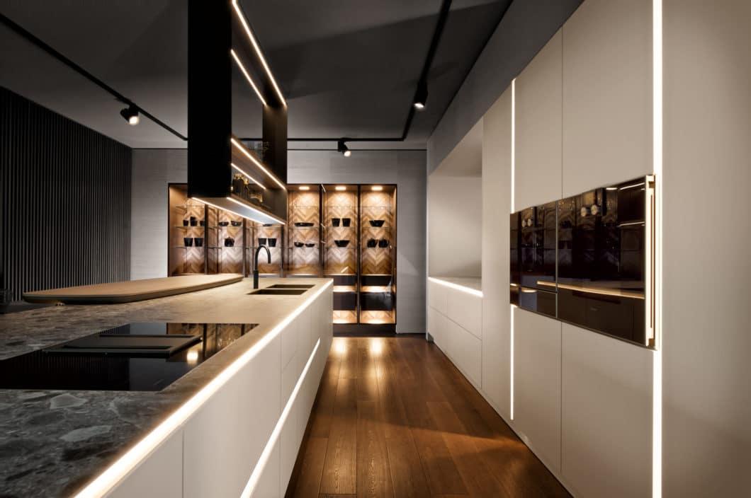 Das Re-Design der minimalistischen PURE-Kollektion brachte eine schräge, illuminierte Eingriffsleiste und wohnliche Vitrinenschränke aus hochwertig parsolbronze getöntem Glas hervor. (Foto: SieMatic)
