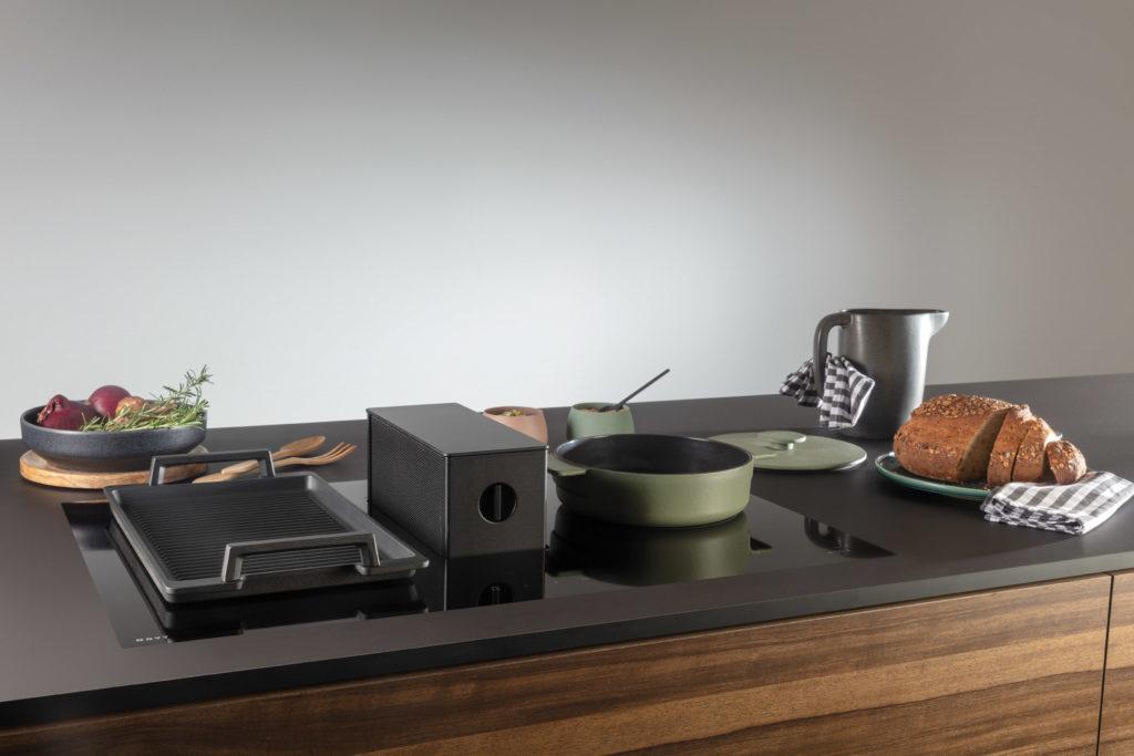 """""""All Black"""": dem Trend zum makellos schwarzen Kochfeld mit integriertem Kochfeldabzug setzte die Novy ONE schon 2016 ein Denkmal. Mittlerweile existiert eine überholte, moderne Turmversion. (Foto: Novy)"""