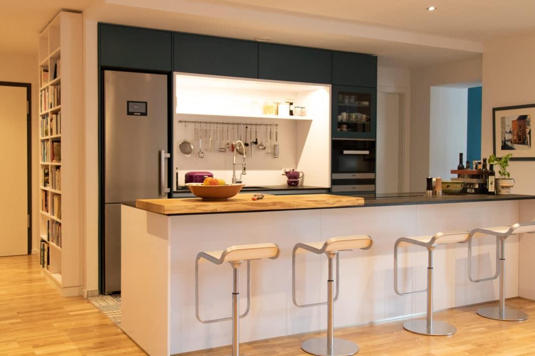 Eine familiäre LEICHT-Küche mit Mattlack-Fronten in Blau und Weiß, Rückwandnische mit LED-Beleuchtung und aufgesetzter Küchenbar aus Holz. (Foto: Küchenhaus Süd)