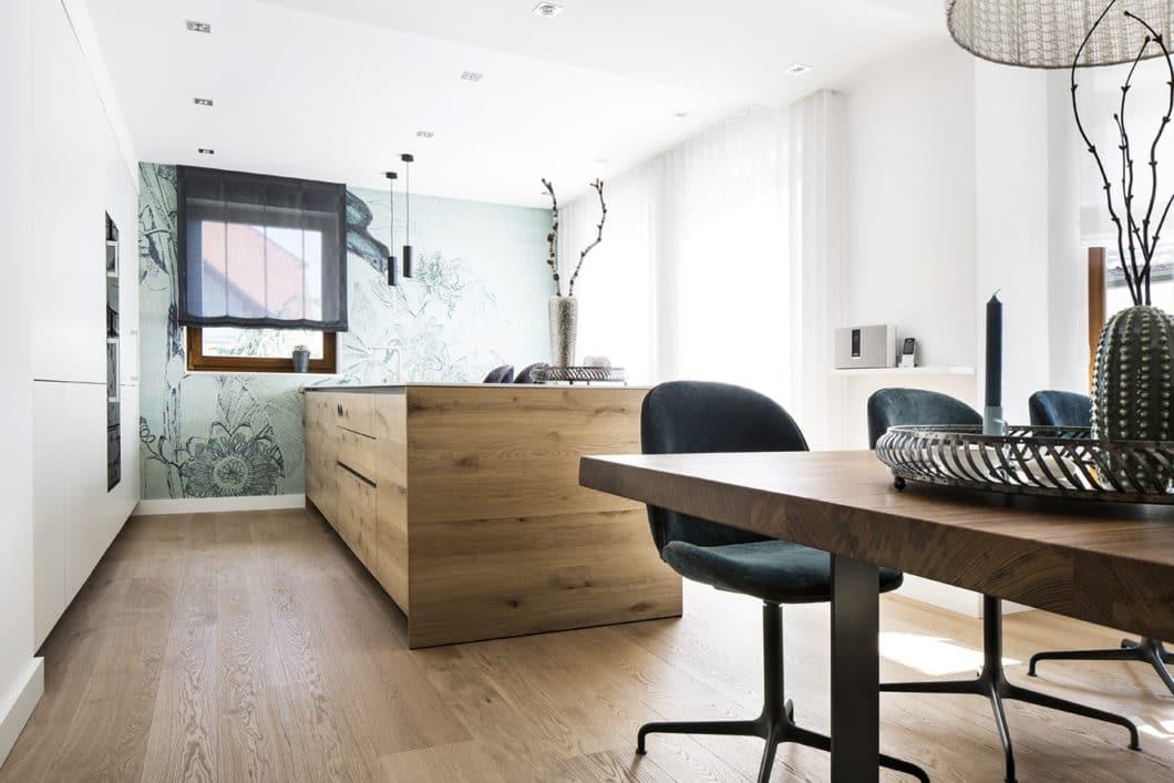 Ein moderner, stilsicher eingerichteter Küchenraum mit einer Kücheninsel aus Holz. Wieviel Aufwand sich dahinter verbirgt, ist auf den ersten Blick kaum sichtbar. (Foto: Dross&Schaffer Ingolstadt)