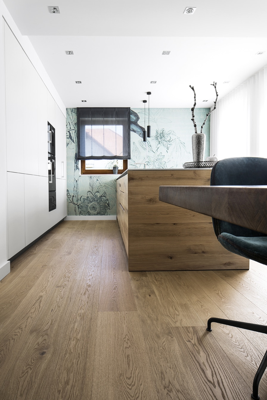 Holz, wohin das Auge blickt: das hochwertige Eichenholz durfte als Parkett im Küchenwohnraum Einzug halten, ebenso wie als Front für die exklusiv gefertigte Kücheninsel aus Holz. (Foto: Dross&Schaffer Ingolstadt)