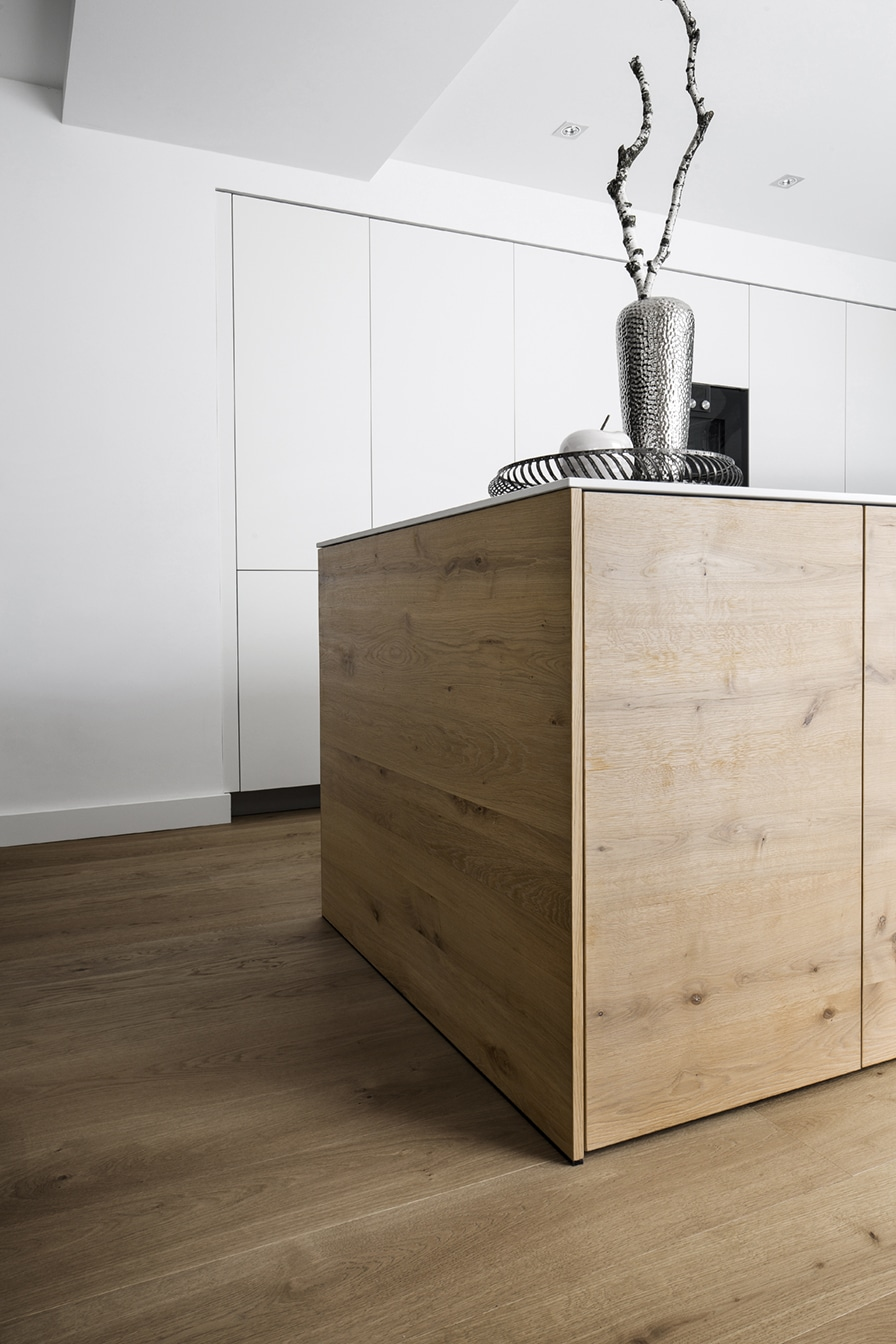 Die elegant handfurnierte Kücheninsel ist von vorn mit einem Tipp-On-Mechanismus ausgestattet, um ein fugenloses Bild zu erzeugen. Im hinteren Bereich ermöglichen abgeschrägte Eingriffleisten den Zugriff auf die Utensilien. (Foto: Dross&Schaffer Ingolstadt)