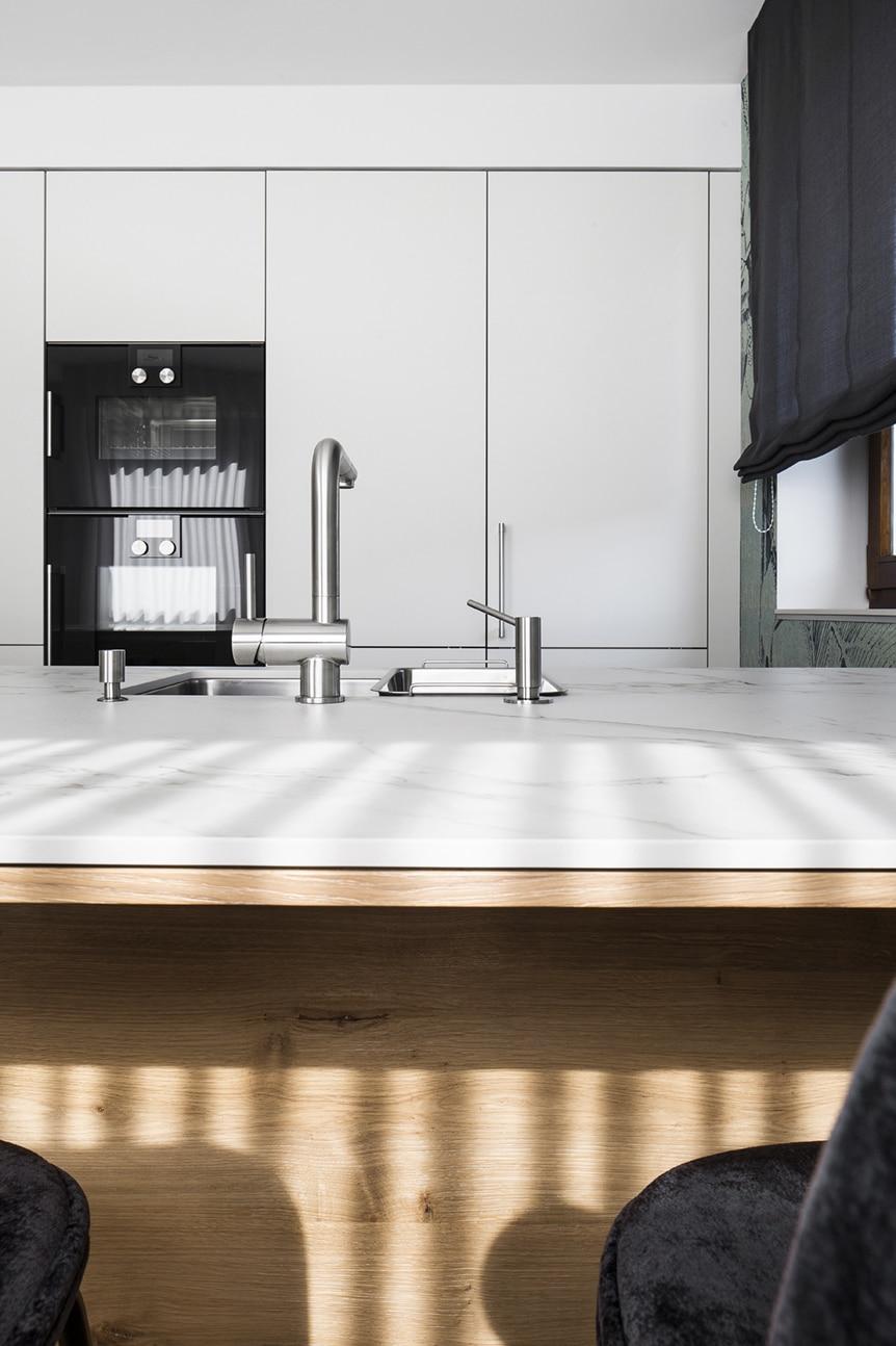 Die Arbeitsplatte aus widerstandsfähigem Dekton wurde dem berühmten italienischen Carrara-Marmor nachempfunden. Zwischen Geräten und Kühlschrank (integriert) sehen Sie die unauffällige Tür zur Speisekammer. (Foto: Dross&Schaffer Ingolstadt)
