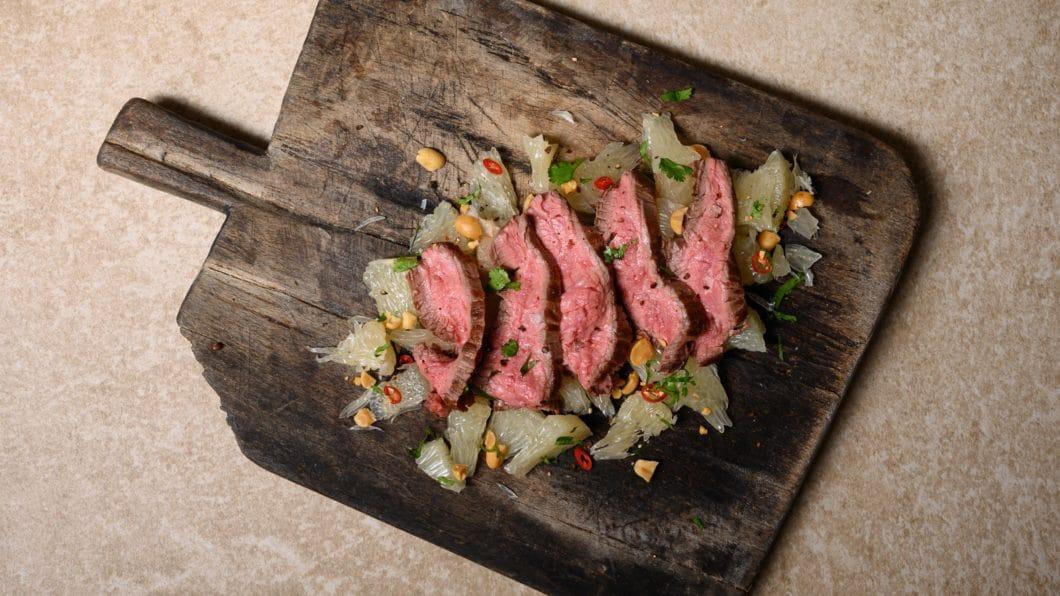 """Australian Flank Steak auf säß-säuerlichem Pomelo-Salat? Diese und viele weitere Rezepte finden sich im BORA-Rezeptheft wieder - natürlich gekocht auf BORA-Modulen inkl. Kochfeldabzug und damit quasi """"an der frischen Luft"""". (Foto: BORA)"""