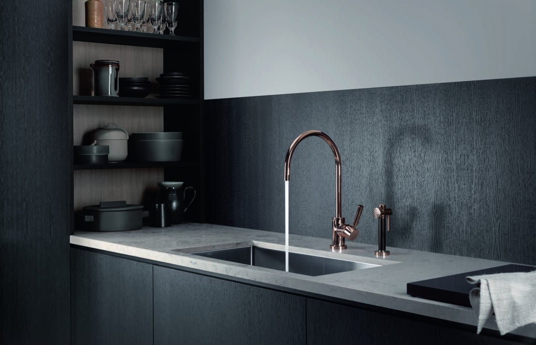 Die elegante, geschwungene Armatur PIVOT in glänzendem Kupfer ist mit 18-karätigem Gold veredelt - eine luxuriöse Antwort auf den Roségold-Trend in der Küche. (Foto: Dornbracht)