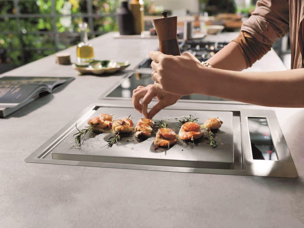 Was ist ein Teppan Yaki? Das Bild stellt es gut dar: auf einer Edelstahplatte werden Lebensmittel wie Fisch, Fleisch und Gewürze schnell und saftig angebraten. (Foto: KitchenAid)