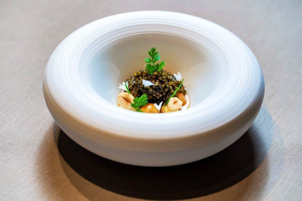 """Speisen, Anrichtung und selbst das Porzellan gehen eine perfekte Symbiose ein unter der Hand von Jan Hartwig. Hier: der """"N25 Kaviar"""". (Foto: V-ZUG)"""