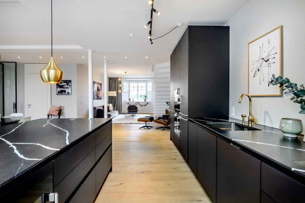 Schwarze Fronten, eine elegante Marmor-Arbeitsplatte und goldene Leuchten lassen diese Küche wie Wohnmöbel wirken. Der angeschlossene Wohnbereich fügt sich dadurch ganz natürlich in das Gesamtbild dieser Wohnküche ein. (Foto: Dross&Schaffer Ludwig 6)