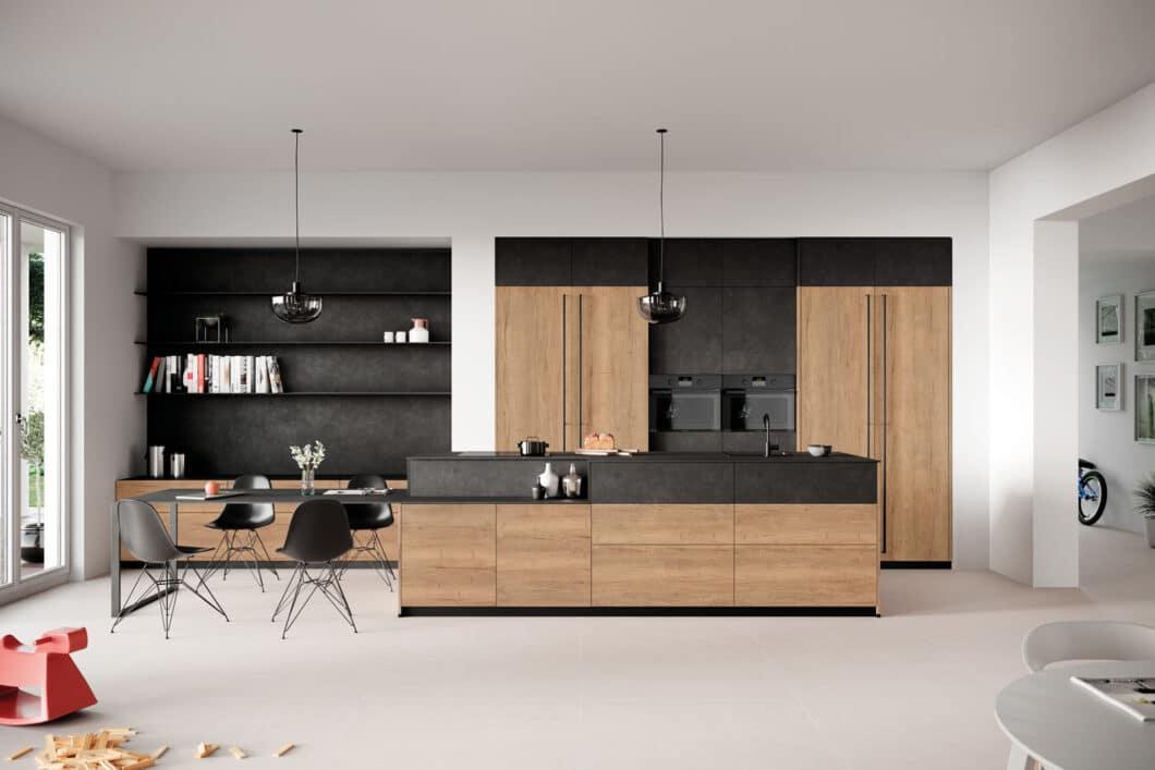 """Holz, Holz, Holz: Eine richtige """"Neuheit"""" mag der Einsatz des warmen Naturmaterials im Küchenraum zwar nicht sein, aber für 2021 setzen die Küchenhersteller verstärkt auf Echtheit statt Optik. Passend dazu, wie im Beispiel von Rotpunkt, auf Schiebetüren, die Geräte verbergen, selbst gestaltete Rückwandsysteme und natürlich die Farbe Schwarz. (Foto: Rotpunkt)"""