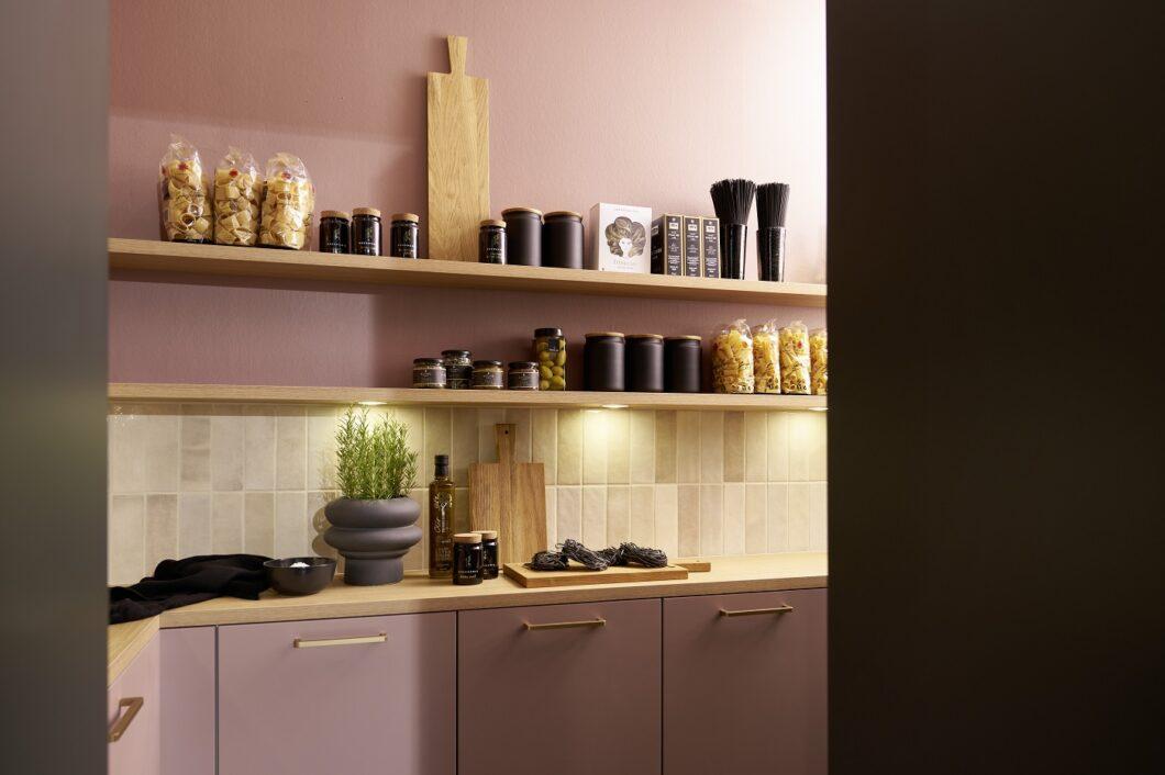 """Mut zur Farbe: rational kreiert einen begehbaren """"Raum im Raum"""", der sich hinter einer Durchgangstür versteckt und kokett mit warmem Rosé und Olive spielt - wohnlich abgerundet mit offenen Eichenholzregalen. (Foto: rational)"""