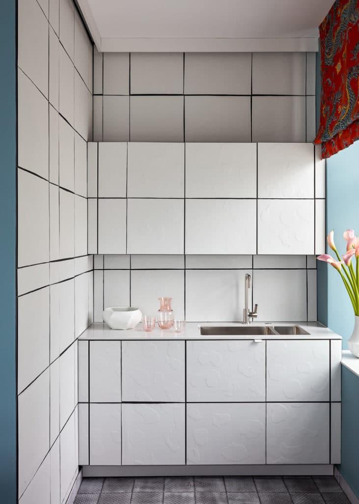 Gekonnt wurden Küchenzeile und Raumumgebung durch den Einsatz von Biskuitfliesen miteinander verwoben. (Foto: Stephan Julliard)
