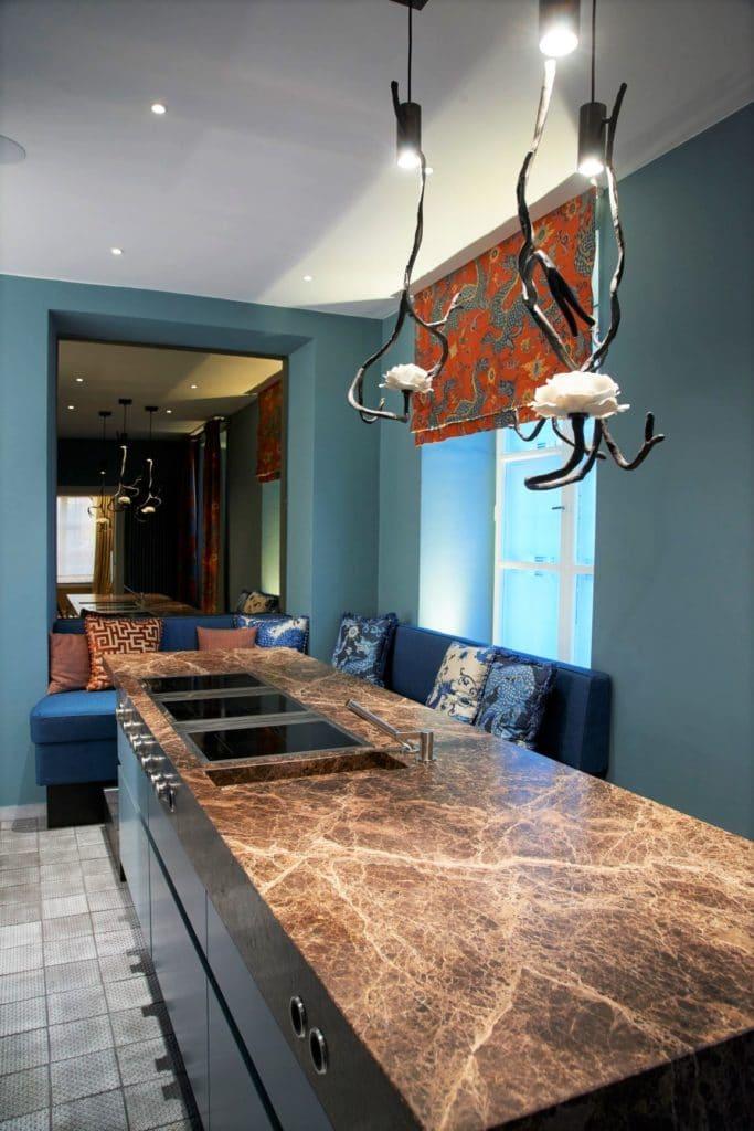 Der Küchenraum von Dross&Schaffer Ludwig 6 wird dominiert von der mächtigen Arbeitsplatte aus braun gesintertem Marmor, die an den Wangen ausläuft. (Foto: Andreas Achmann)