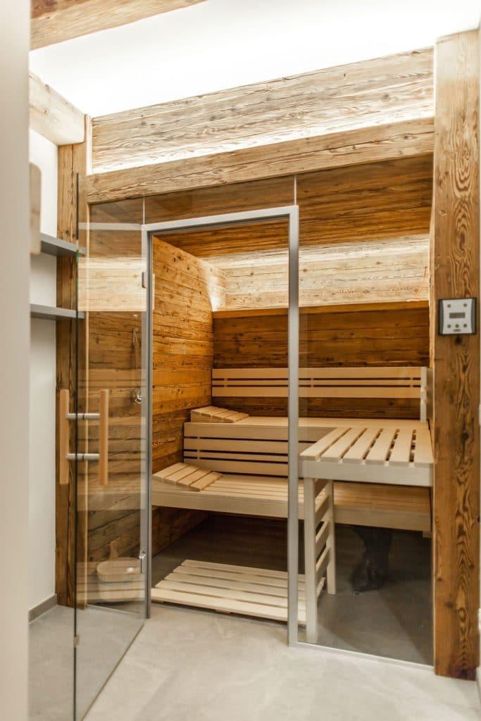 Die Sauna des Herstellers TPI aus dem oberösterreichischen Frankenburg verkleidete Hannes Vötter mit Altholz. Der Hinterwand-Ofen ist dabei geschickt versteckt und ebenfalls mit gehacktem Altholz ummantelt. (Foto: The Kitchen Club)