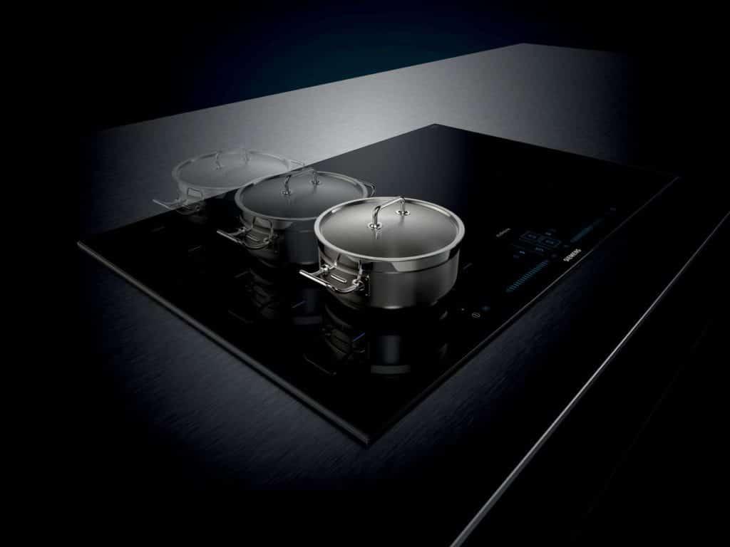 Ein Induktionskochfeld leitet die Wärme durch den Topfboden und erhitzt das Gargut gleichmäßig an allen Stellen. Neuere Modelle lassen die Töpfe sogar beliebig hin- und herschieben auf dem Kochfeld - sie werden automatisch erkannt. (Foto: Siemens Hausgeräte)
