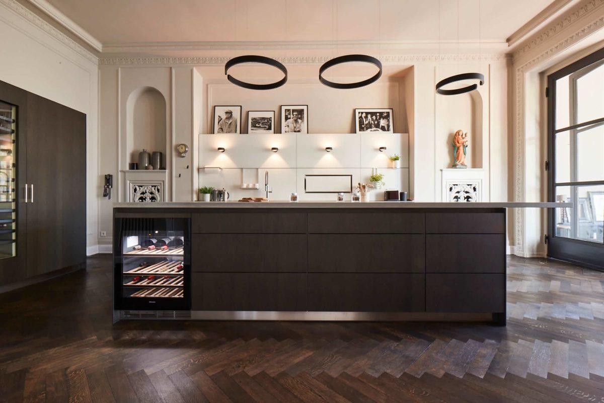 Spektakuläre Planung aus Hamburg. Sicher, eine Altbauwohnung ist nicht die schlechteste Grundlage für eine hochwertige Küche. Der Fokus liegt hier aber vor allem auf der Lichtplanung - Designleuchten sind 2021 ein großer Trend in der Küche. Zudem wurde auf Eiche schwarzgrau als Frontmaterial gesetzt. (Foto: Küchen-Atelier Hamburg)