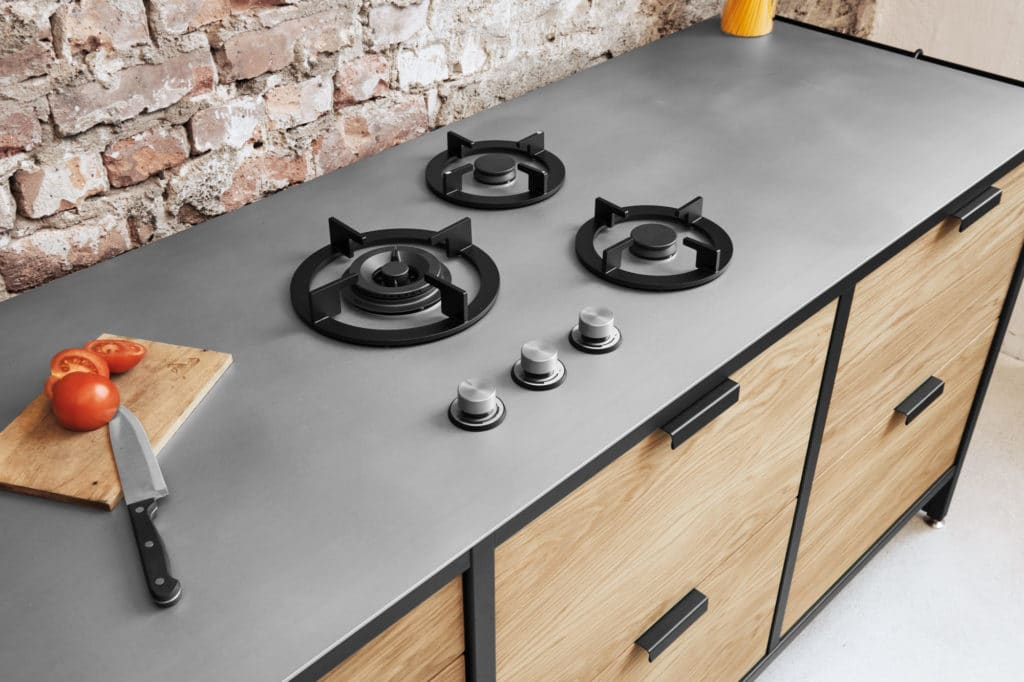 Edelstahl in der Küche ist nicht nur hochgradig hygienisch, sondern vor allem hitzefest, säurebeständig, schlagfest. Das lädt zu kreativen Planungsideen ein, beispielsweise der integrierten Kochzone auf der Arbeitsplatte. (Foto: Manufaktur Jan Cray)