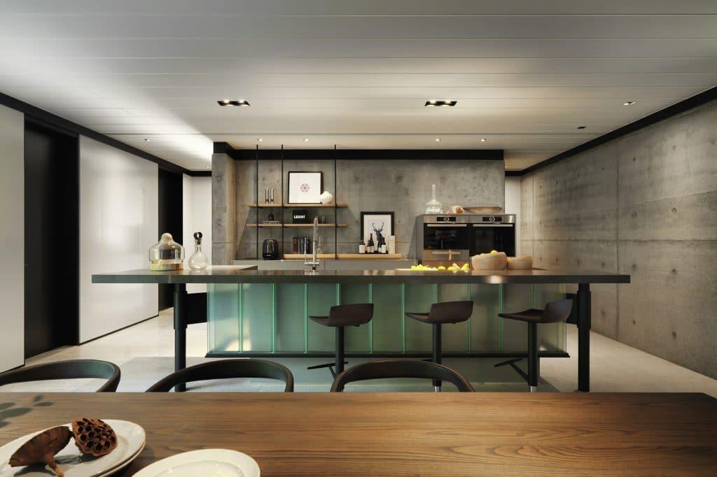 Reduzieren Sie den Küchenraum auf einige wenige Farbtöne. Hier dominieren dunkle Farben in Schwarz und Beton den Raum - und werden vom hellen Holz und Grün aufgelockert. (Foto: LEICHT)