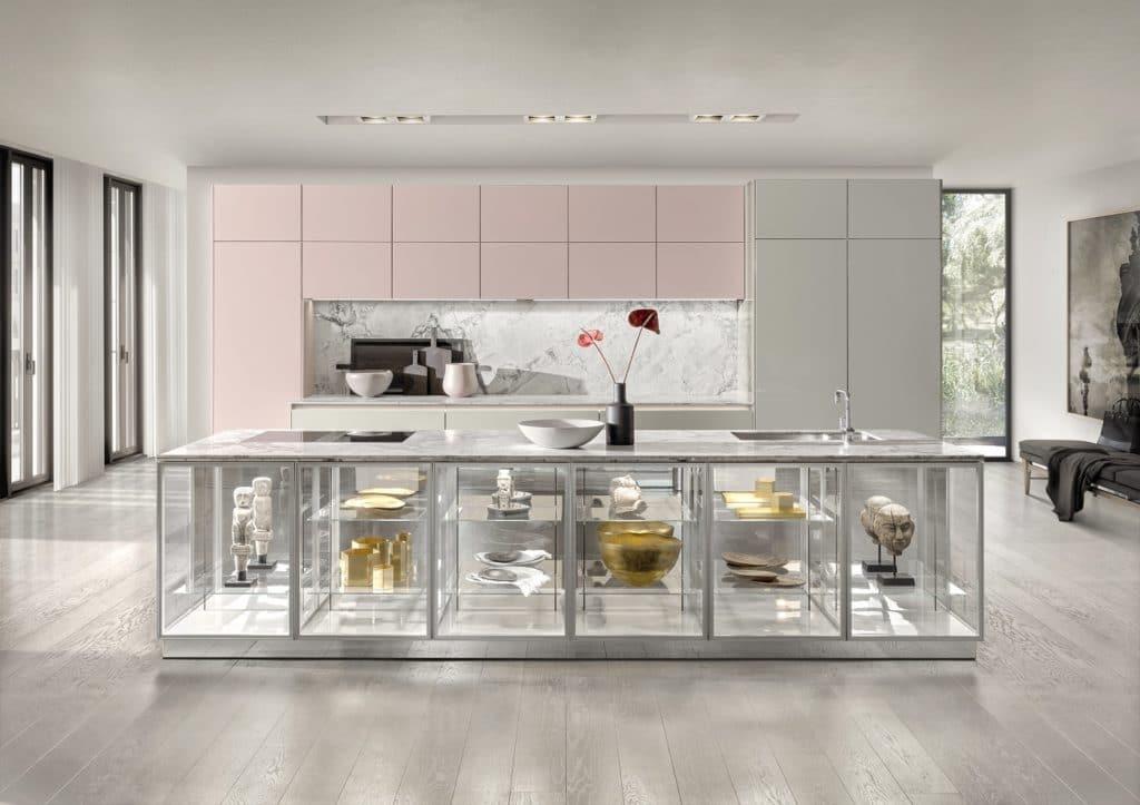 Ein blumiges Rosé und ein heller Kieselgrau-Ton gehen eine ungewöhnliche Liaison ein. Aufregender gestaltet sich da die halboffene Kücheninsel aus Edelstahl und Glas. (Foto: SieMatic)
