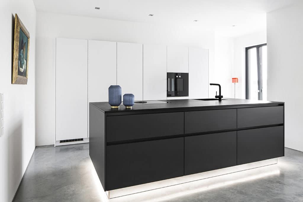 Wie Yin und Yang fügen sich die schmale, grifflose Hochschrankwand in Mattlack Weiß und die monumentale, schwarze Kücheninsel zusammen. Besonderes Highlight ist die erhabene Unterbodenbeleuchtung des Kochblocks. (Foto: Dross&Schaffer Ingolstadt)