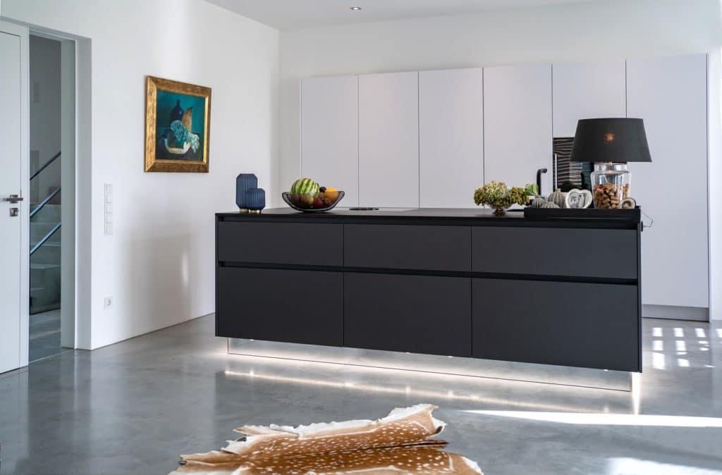Mattpolierter Estrich und weiße Wände bieten die puristische Ausgangsbasis für eine kunstvolle Ausgestaltung von Raum und Küche. (Foto: Thomas Neumann/Küchen&Design Magazin)