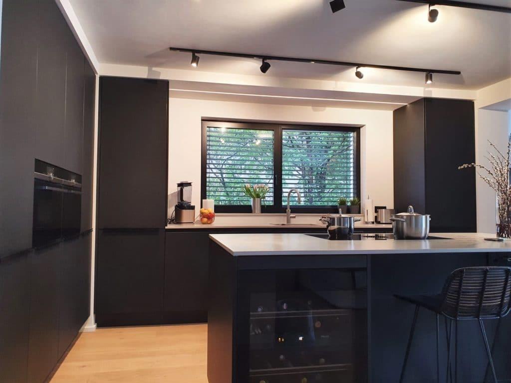 Gekocht wird mit Blick in den offenen Wohnraum - dank eines integrierten Kochfeldabzugs stört kein sperriger Dunstabzug das minimalistische Küchenbild. (Foto: Dross&Schaffer München Ost)