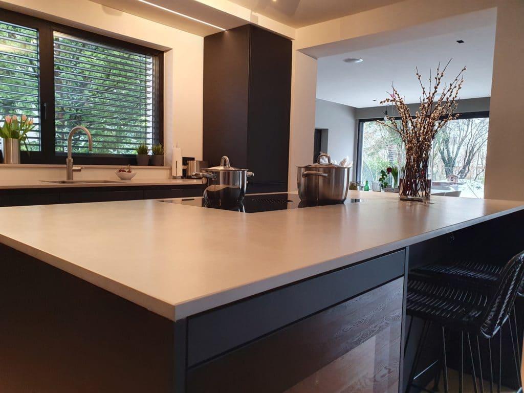 Die schwarze Küche öffnet sich nicht nur zum offenen Wohnraum hin, sondern rechterhand auch zu einem gesonderten und lichtdurchfluteten Essbereich. (Foto: Dross&Schaffer München Ost)