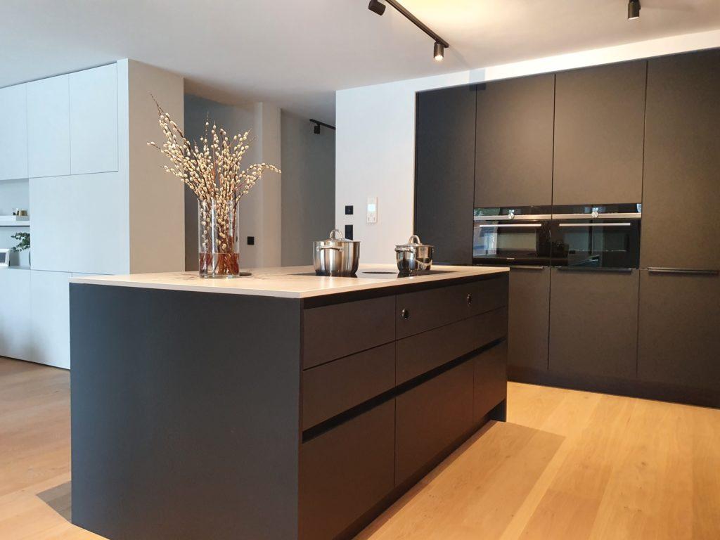 Der Übergang von Küche zu Wohnraum erfolgt im Farbdreiklang Schwarz-Weiß-Holz. Auch die flächenbündige Schrankintegration bleibt als leitendes Designelement bestehen. (Foto: Dross&Schaffer München Ost)