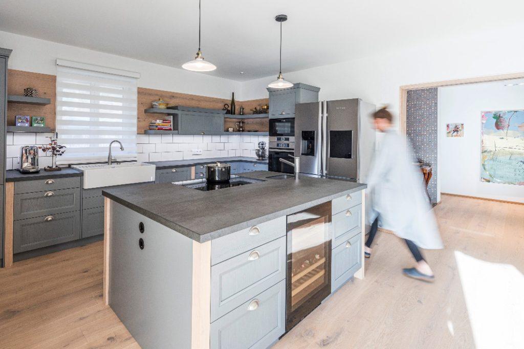 Konsequente Designlinie: Das Eichenholz der Bodendielen findet sich auch in den Wangen der Küchenmöbel und als Wandverkleidung wieder. So entsteht der Eindruck eines maßangefertigten Unikats. (Foto: WohnHaus Grill & Ronacher)