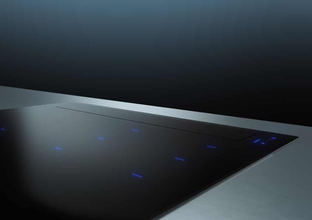 Eine puristische Einheit mit klarer, flächenbündig eingebetteter Kante: die glassdraftAir-Tischlüftung passt sich dem planen schwarzen Kochfeld exakt an. (Foto: Siemens Hausgeräte)