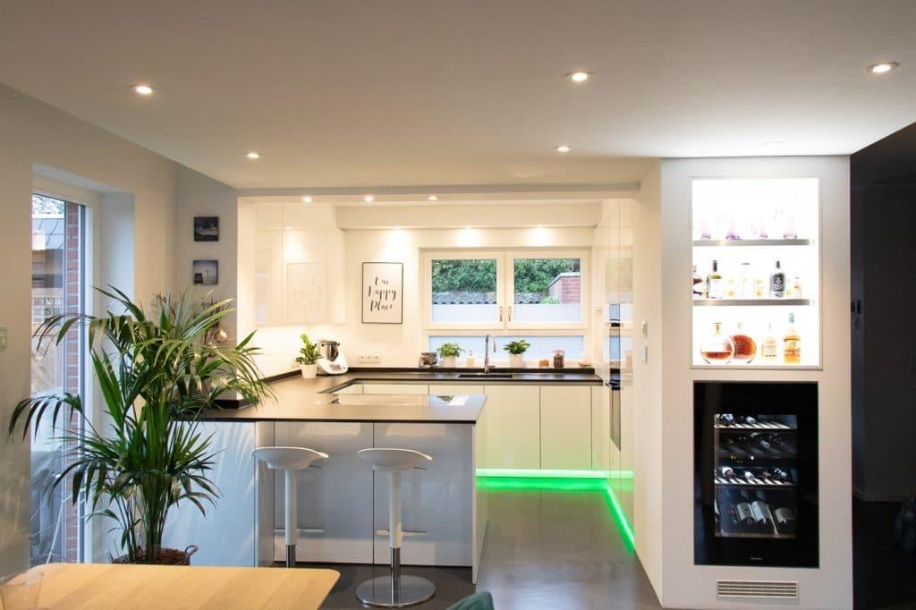 Ein grünes LED-Band unterhalb der Unterschränke setzt den Küchenraum von Wohnbereich ab und sorgt für Stimmung. Auch praktisch: eine Bar-Nische fürs schnelle Frühstück. (Foto: Küchenhaus Süd)