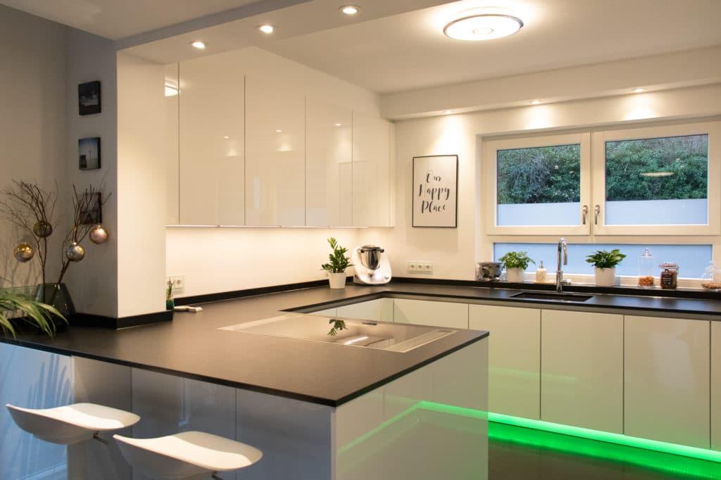 Modern, minimalistisch und dennoch wohnlich. Weißer Hochglanzlack reflektiert das Tageslicht; die schwarze Granit-Arbeitsplatte ist belastbar und hochwertig. (Foto: Küchenhaus Süd)